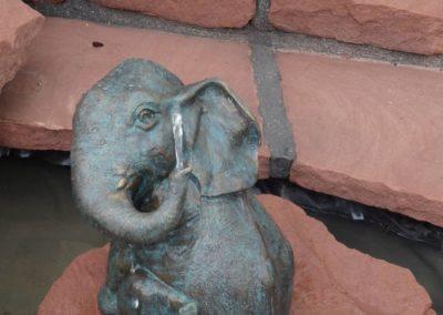 k-Bronzefigur Akasha auf Findling